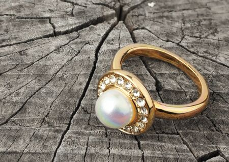 diamond ring: Jewellery ring with pearl on grey wood background