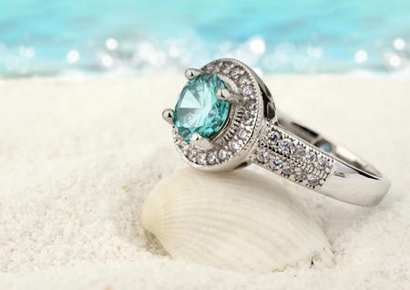 Juwelenring met aquamarijngem op zandstrandachtergrond Stockfoto