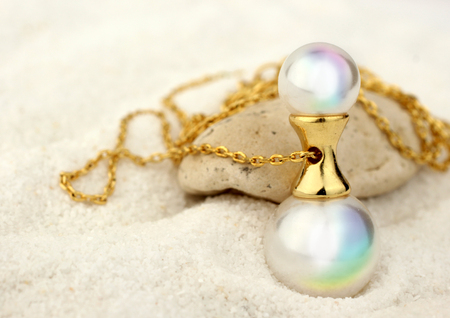 Golden Jewelery pendant with pearls on sand background, copy space Stock Photo