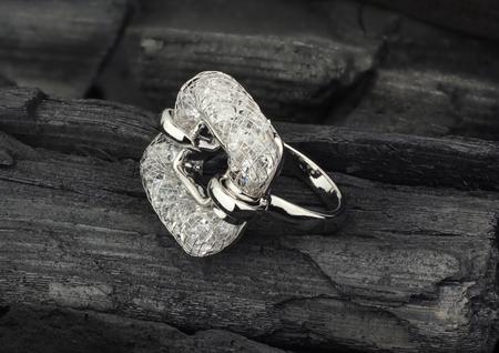 Anello di gioielli in oro con diamanti, su carbone nero come sfondo