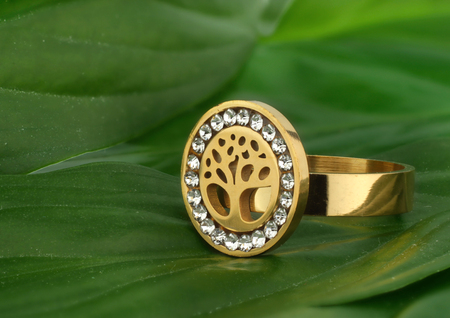 Jewelry ring with diamonds, shape of tree, on leafs background Archivio Fotografico