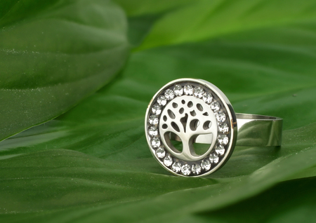 Jewelry ring with diamonds, shape of tree, on green leafs