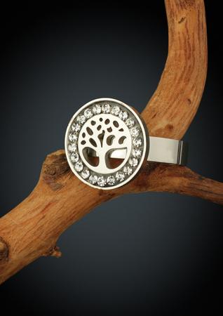 Jewelry ring shape of tree on twig, on dark