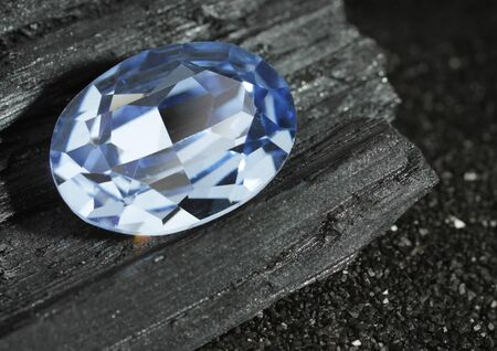 faceted blue jewelry gemstone sapphire on black background