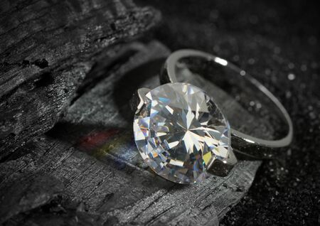 Jewelry ring with big diamond, on black coal texture background