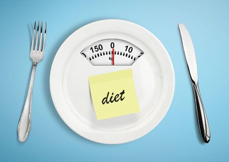 Diet and weight loss concept. Plate with scale weighing-machine on blue