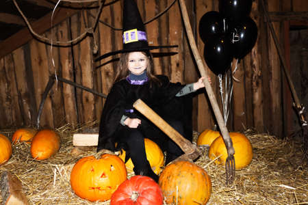 Little girl in black halloween hat and black clothing with pumpkin on attic.