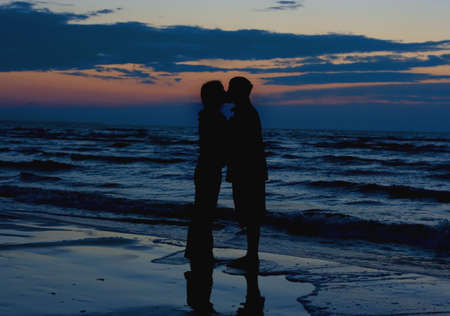 Couple kissing near sea. photo