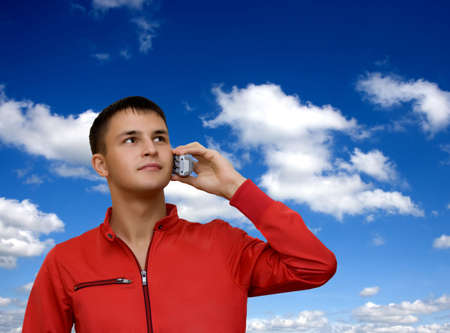 Attractive young man holding out cellphone and looking at blue sky. Free space for your text. photo