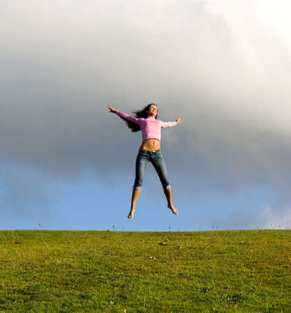 Happy young beautiful girl jumping in the green field.  Stock Photo - 1357947