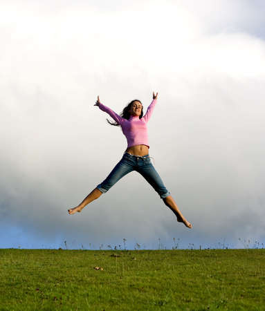 Happy young beautiful girl jumping in the green field.  photo