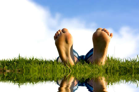Feets on grass near water. Stock Photo - 1357917