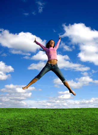 Happy young beautiful girl jumping in the green field.  Stock Photo - 1397939