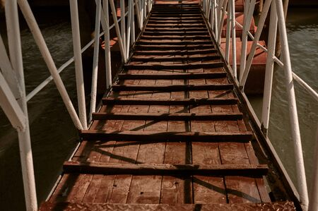 wooden bridge with metal railing against the background of the water along which they descend to the boat. gangway, promenade.