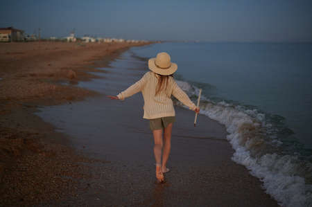 Girl runs on the beach next to the waves at sunset . High quality photo Banque d'images
