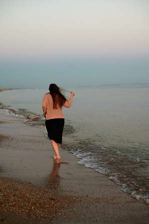 Woman walks along the beach next to the waves at sunset Banque d'images