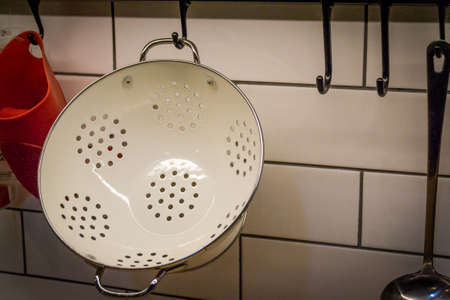 A white metal colander, a kullerder or strainer is hanging on the kitchen wall. Eat.