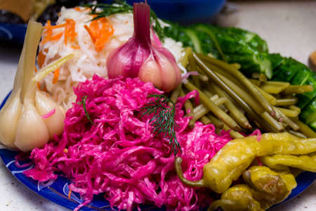 Russian snack: sauerkraut with beet and vegetables: garlic, cucumber, chili pepper on the table. Celebration.