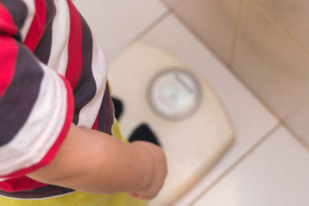 The child stands on the floor scales in a striped T-shirt, the view from the top. Health Standard-Bild