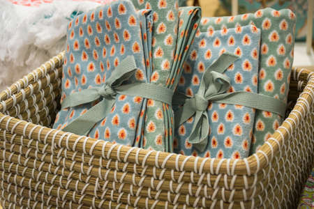 Gift towels with a dot pattern, tied with braid in a wicker basket.