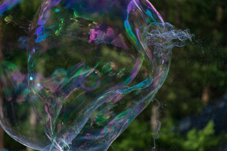 Iridescent large soap bubbles against the background of the forest. Entertainment. Banco de Imagens