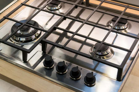 Chrome plate of gas cooker. Four control knobs. Kitchenware. Comfort Banco de Imagens