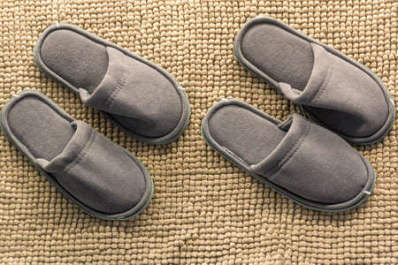 Two pairs of gray homemade slippers isolated on a brown background. Home cosiness. Banco de Imagens