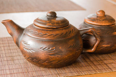 A beautiful clay teapot with an orienic pattern. Tea drinking. Creation.
