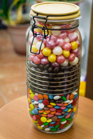 A large container with colorful candies with a tight-fitting lid. Sweets, Banco de Imagens