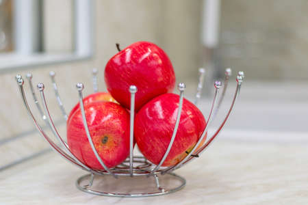 Bright red apples in the original metal vase. Kitchen table. Banco de Imagens