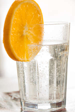 A glass of soda water and a slice of orange. Fresh. Banco de Imagens