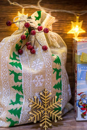 Bag with Christmas gifts, illuminated with garlands.