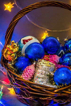 Wicker basket with colored Christmas toys illuminated with festoons. Banco de Imagens