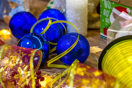Christmas background with decorations in the form of balls of ribbons and candles on a wooden board.