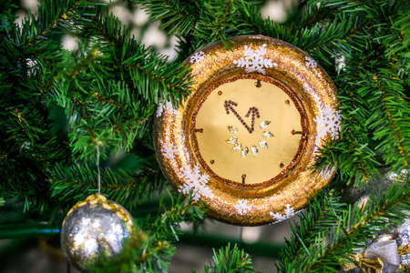 Christmas watch with a winter decoration on the Christmas fir. Happy new year concept.