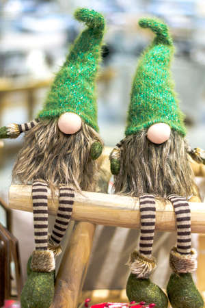 Christmas gnomes in green caps and striped pants. Sit on a wooden stool