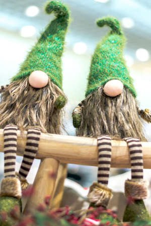 Christmas gnomes in green caps and striped pants. Sit on a wooden bench. Christmas