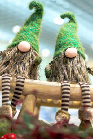 Christmas gnomes in green caps and striped pants. Sit on a wooden bench. Christmas. Holiday.