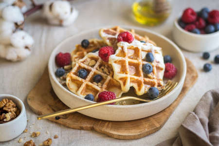 A sweet waffle dessert decorated with berries and nuts in a beautiful sauce-pan on a canvas tablecloth. Natural light