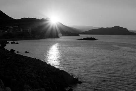 Sunrise from behind the mountains against the backdrop of the sea and the Istavers. Black and white image
