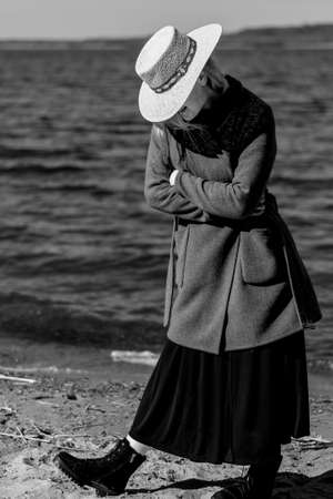 The girl on the shore of the reservoir in a straw hat and coat. Black and white photography Banco de Imagens