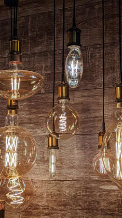 Burning light bulbs with original beautiful spirals on a warm brown background. Disain, beauty and comfort indoors