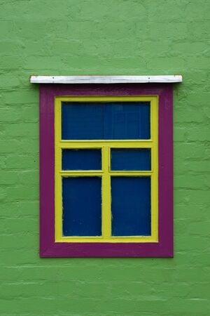 Beautifully decorated old window on a green wall. Unusual decoration. Vertical orientation