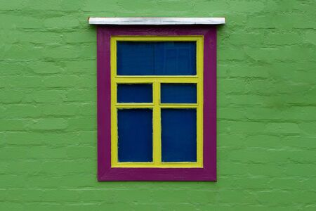 Beautifully decorated old window on a green wall. Unusual decoration. Horizontal orientation