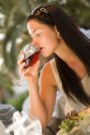 Young Beautiful woman tasting red wine at restaurant (shallow dof) photo