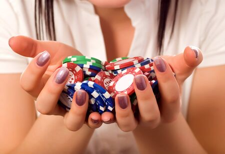 girls hands holding a bunch of poker chips (focus on front) photo