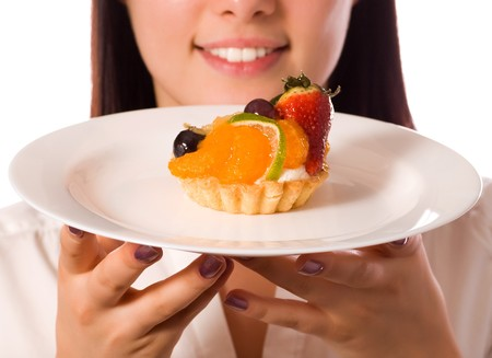 young woman with low-calorie fruit cake (focus on cake) photo