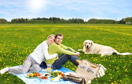 vegetables young couple: Couple at picnic with golden retriever