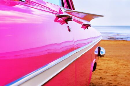Classic pink car at beach photo