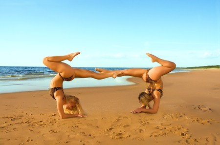 contortionist: Two acrobatic girl on the beach